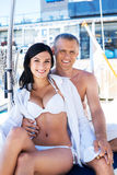 Rich man and a beautiful woman in swimsuits on a boat Royalty Free Stock Photos