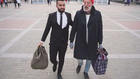 Rich man decided to help poor man. Young bearded man in black suit with beggar senior male.