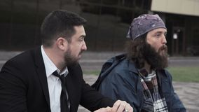 Rich man eating next to a beggar while waiting. Successful rich young man eating on the sidewalk next to a bearded homeless beggar while waiting and looking up stock video footage