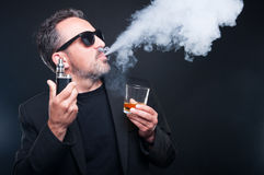 Rich man exhaling vapor from an electronic cigarette Royalty Free Stock Images