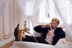 Rich man in expensive apartments. Handsome blond man in elegant black suit posing in classical vintage interior. Young man lying in bath at home stock photo