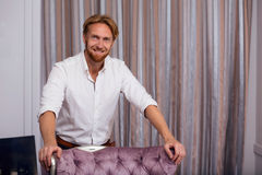 Rich man in expensive apartments. Portrait of handsome fashionable man posing in classic interior. Blond man in white shirt toothy smiling for camera royalty free stock photography
