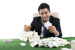 The rich man holding whiskey glass and show winning with cards stock photos