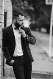 Rich man in a jacket near his house. A rich man with a beard smokes electronic cigarette stock image