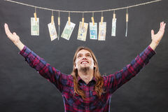 Rich man with laundry of money. Riches and fortune. Young happy man with a lot of money on black background. Winning the lottery concept stock photos