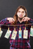 Rich man with laundry of money. Riches and fortune. Young happy man with a lot of money on black background. Winning the lottery concept royalty free stock image