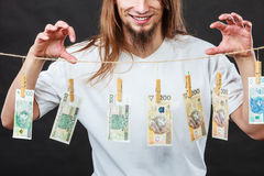 Rich man with laundry of money. Riches and fortune. Young happy man with a lot of money on black background. Winning the lottery concept stock photo