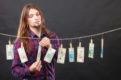 Rich man with laundry of money. Riches and fortune. Young happy man with a lot of money on black background. Winning the lottery concept stock photography