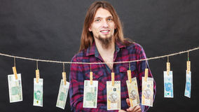 Rich man with laundry of money. Riches and fortune. Young happy man with a lot of money on black background. Winning the lottery concept royalty free stock photography