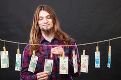 Rich man with laundry of money. Riches and fortune. Young happy man with a lot of money on black background. Winning the lottery concept royalty free stock photos