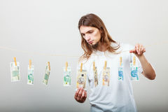 Rich man with laundry of money. Riches and fortune. Young happy man with a lot of money on grey background. Winning the lottery concept stock photo