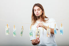 Rich man with laundry of money. Riches and fortune. Young happy man with a lot of money on grey background. Winning the lottery concept stock image