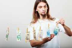 Rich man with laundry of money. Riches and fortune. Young happy man with a lot of money on grey background. Winning the lottery concept royalty free stock photo