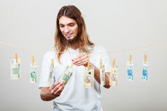 Rich man with laundry of money. Riches and fortune. Young happy man with a lot of money on grey background. Winning the lottery concept stock photos