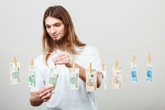 Rich man with laundry of money. Riches and fortune. Young happy man with a lot of money on grey background. Winning the lottery concept royalty free stock photos