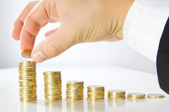 Rich man. Mann stacking coins on a table stock images