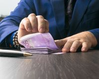 Man in Men's Suits.Bribe and corruption with euro banknotes. Rich man in Men's Suits with bracelets, pen in table. Bribe and corruption with euro banknotes stock image
