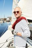Rich man at own yacht. Serious rich mature man in stylish outfit wearing in gloves holding rope and looking at camera while standing on own yacht stock image