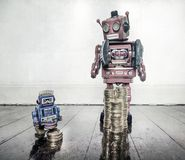 Rich poor robots. Rich man poor man concept with retro robots on a old wooden floor with reflection royalty free stock photos