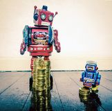 Rich poor robots. Rich man poor man concept with retro robots on a old wooden floor with reflection stock photo