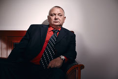 Rich man portrait. Serious middle aged businessman wearing black suit, red shirt and wristwatch sitting on old fashioned sofa in office and looking aside royalty free stock images