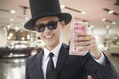 Rich Man sorridente con un grande cappello che tiene e che ostenta i suoi soldi Immagini Stock