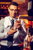 Rich man standing in his bar and holding bottle of alcohol. Standing in bar. Rich successful man standing in his bar and holding bottle of alcohol stock photography