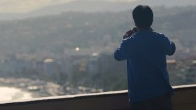 Rich man standing on luxury hotel room balcony and making photos of city view. Stock footage stock video