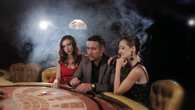 The rich man surrounded by two prostitutes play in a casino stock footage