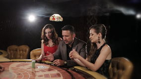 The rich man surrounded by two prostitutes to play and win at the casino. The rich man surrounded by two prostitutes play in a casino stock video footage