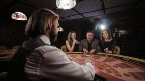 The rich man surrounded by two prostitutes to play and win at the casino. The rich man surrounded by two prostitutes play in a casino stock footage