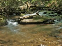 Rich Mountain Creek in Stone Mountain State Park. Water cascades over mossy rocks in Rich Mountain Creek.  Stone Mountain State Park in Low Gap, North Carolina Stock Image