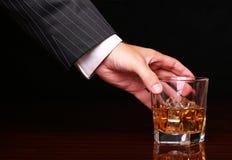 Rich och innehav för framgångaffärsman i handexponeringsglas av whisky Arkivfoton