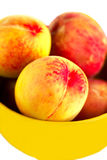 Rich peach in the yellow plate Royalty Free Stock Photos