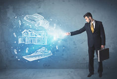 Rich person throwing hand drawn car yacht and house Royalty Free Stock Photography