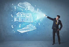 Rich person throwing hand drawn car yacht and house Royalty Free Stock Photo
