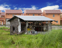 The rich and the poor. Lone nipa hut in contrast to rising subdivision houses Stock Image