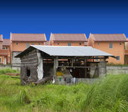 The rich and the poor. Lone nipa hut in contrast to rising subdivision houses Royalty Free Stock Photography