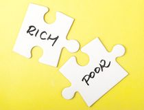 Rich and poor words. Written on two pieces of jigsaw puzzle stock photos