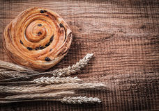 Rich raisin bakery bunch of wheat ears on oak wooden board food Royalty Free Stock Images