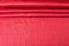 Rich red wavy fabric background. Stock Photo