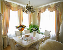Rich room. Windows, a table, curtains royalty free stock photo