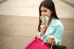 Rich shopaholic beautiful woman with banknotes. Asian happy shopaholic woman hold shopping bags and many money banknotes, US dollar bills, and copy space for stock photos