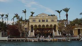 Looking across to the luxurious waterfront mansion with palm trees and private dock in sunny isles beach,miami. Rich storied villa among tropical trees on the stock video