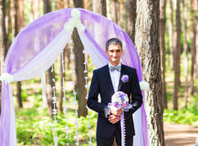 Rich stylish groom with bridal bouquet waiting bride near the wedding arch Royalty Free Stock Photography