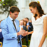 Rich stylish groom and bride  put ring near the arch of sunflowe Stock Photos