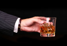 Rich and success business man holding in hand glass of whiskey Royalty Free Stock Photography