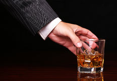 Rich and success business man holding in hand glass of whiskey. Rich and success business man holding in hand glass of alcohol scotch whiskey with ice cube on stock photos