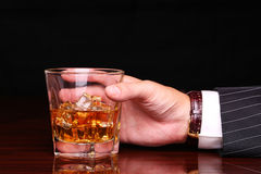 Rich and success business man holding in hand glass of whiskey Royalty Free Stock Photo