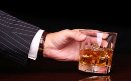 Rich and success business man holding in hand glass of whiskey Royalty Free Stock Image